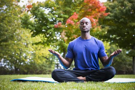 soustředění: mladý černý muž nosí atletické oblečení sedí v parku cvičení jógy