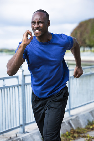 hacer footing: young black man wearing athletic wear running around the lake