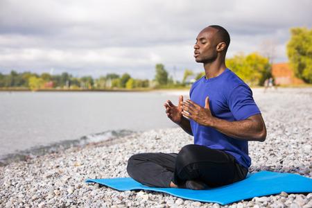utthita: young black man wearing athletic wear sitting on the beach exercising yoga