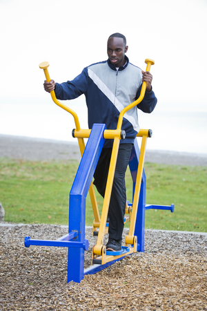 Active black man in training suit exercising on elliptical trainer machine at outdoor gym Stock Photo
