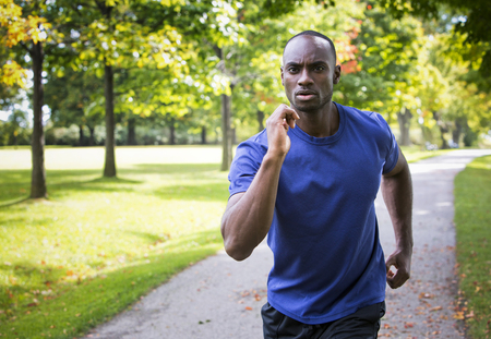 black male: young black man wearing athletic wear running in the park