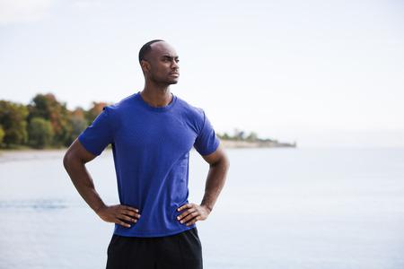 jonge zwarte man met atletische slijtage op het strand