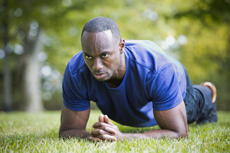athletic wear: young black man wearing athletic wear doing exercise in the fall park