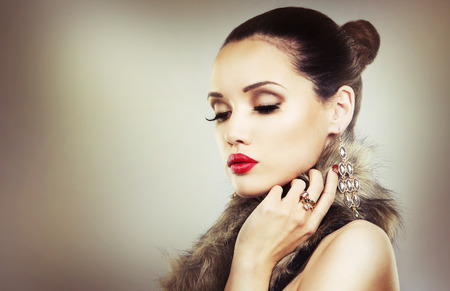 luz roja: Upscale woman wearing gold jewellery and red lipstick on light background