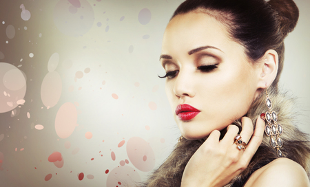 luz roja: Mujer de lujo de usar la joyería de oro y el lápiz labial de color rojo sobre fondo claro Foto de archivo