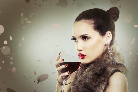 beautiful woman with dark makeup and red lipstick posing on light grey background. Drinking glass of red wine. Stock Photo