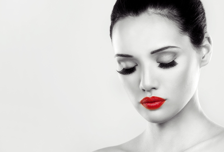 white color: beautiful woman with dark makeup and red lipstick posing on light grey background. Black and white image.