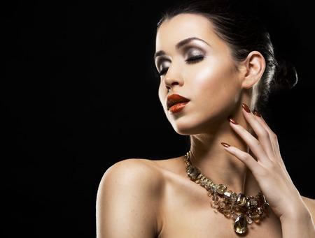 nailpolish: romantic woman with golden makeup and nailpolish. Big gold fashion necklace. Black isolated background. Stock Photo
