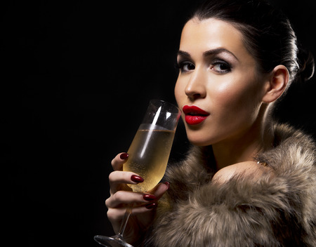 romantic woman with golden makeup and nailpolish. Big gold fashion necklace. Black isolated background. Holding glass of champagne