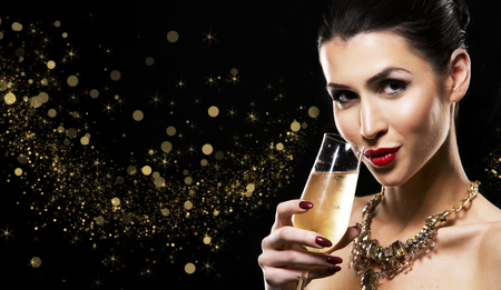 nailpolish: romantic woman with golden makeup and nailpolish. Big gold fashion necklace. Black isolated background. Holding glass of champagne