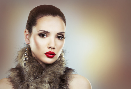 Upscale woman wearing gold jewellery and red lipstick. Winter fur scarf. Light background. Party