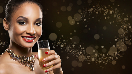 nailpolish: romantic Indian woman with golden makeup and nailpolish. Big gold fashion necklace. Black isolated background. Holding glass of champagne.