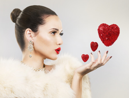 aretes: Upscale woman wearing gold jewellery and red lipstick. Red hearts. Light background. Foto de archivo