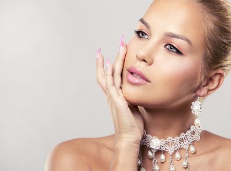 Belle femme avec le maquillage sombre et rouge à lèvres rose posant sur fond clair portant mariée printemps et en été collier bijoux Banque d'images - 71927117