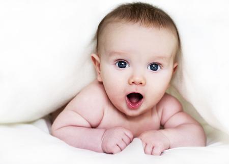 baby boyl is hiding under the white blanket Standard-Bild