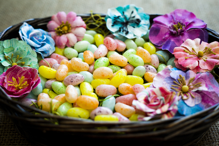 blooming  purple: arrangement of colorful easter jelly bean eggs and flowers laid in basket Stock Photo
