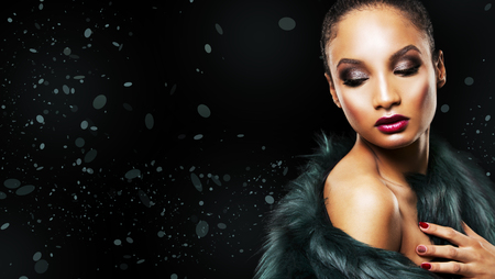 upscale: Upscale Indian woman wearing green fur coat and dramatic red lipstick on black background
