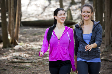 young fit caucasian women exercising outdoors. Hiking. Natural settings in the woods. 免版税图像