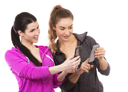 young casual caucasian women wearing sport outfits on white isolated background. Holding mobile phones. photo