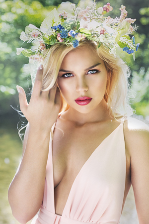 beautiful woman with pretty makeup and pink lipstick posing outdoors wearing spring and summer dress and flower crown