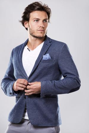 밝은 배경에 세련된 재킷 유행 헤어 스타일 잘 생긴 남자의 패션 초상화