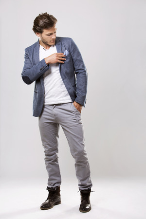 Fashion portrait of a handsome man with trendy hairstyle in a stylish jacket on light background
