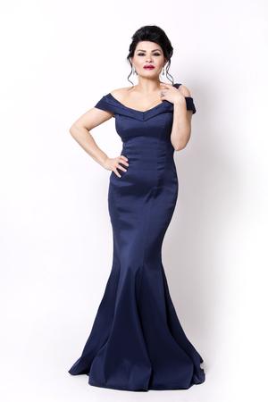 elegant woman wearing evening gown in dark blue or navy color on white background Standard-Bild