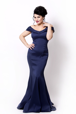elegant woman wearing evening gown in dark blue or navy color on white background Stockfoto