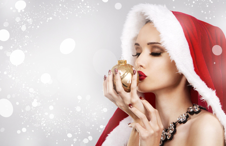Upscale woman in Santa Claus theme outfit holding Chrsimas gold ornament on winter background with snow.