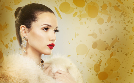 Upscale woman wearing gold jewellery and red lipstick on golden background Standard-Bild