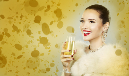 Upscale woman wearing gold jewellery and red lipstick on gold background Standard-Bild