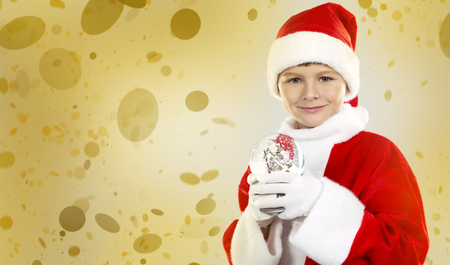 caucasian boy in Santa Claus theme outfit holding Chrsimas ornament on winter background with snow.