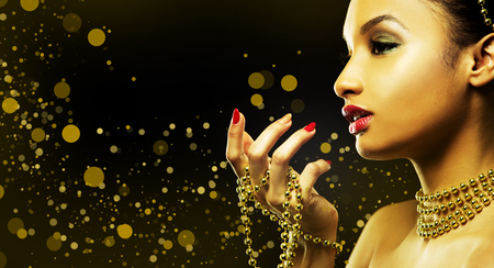 Upscale Indian woman wearing gold jewellery and red lipstick on golden background Standard-Bild