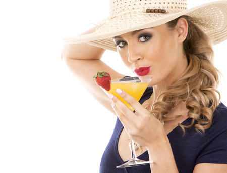 beautiful woman with dark makeup and red lipstick posing on white background wearing bright blue swimsuit and hat. Holding drink.  Standard-Bild