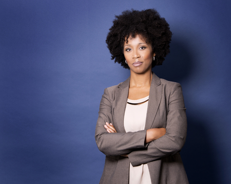 beautiful casual black woman wearing jacket and jeans on dark blue background