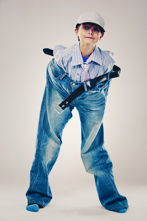 Kaukasische jongen die het overhemd, de jeans en de band van zijn Papa op lichte achtergrond draagt. Hij draagt grote kleding voor volwassenen die te groot voor hem is.