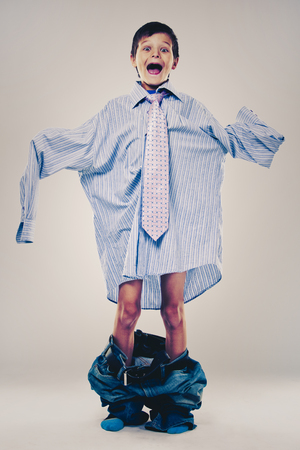 Caucasian boy wearing his Dads shirt, jeans and tie on light background. He is wearing big adult size clothes which are too big for him. 版權商用圖片
