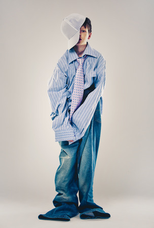 Caucasian boy wearing his Dads shirt, jeans and tie on light background. He is wearing big adult size clothes which are too big for him. Stock Photo