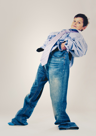 Caucasian boy wearing his Dad's shirt, jeans and tie on light background. He is wearing big adult size clothes which are too big for him. Foto de archivo