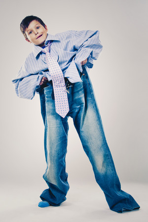 Caucasian boy wearing his Dad's shirt, jeans and tie on light background. He is wearing big adult size clothes which are too big for him. Standard-Bild