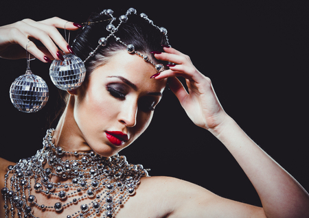 beautiful woman with dark makeup and red lipstick posing on black background. Wearing silver disco ball jewllery.  Banque d'images