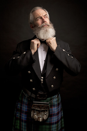 Close up of senior man with grey hair and full beard, wearing scotting kilt on dark background Banco de Imagens