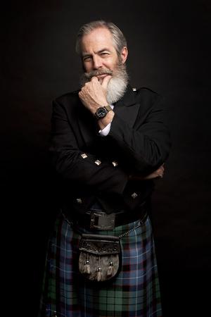 Close up of senior man with grey hair and full beard, wearing scotting kilt on dark background Stock Photo