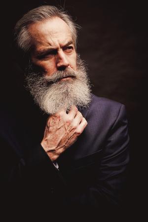 Close up of senior man with grey hair and full beard, wearing suit on dark background Zdjęcie Seryjne