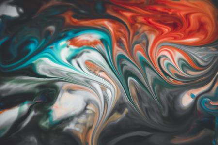Colorful liquid paints mixed together creating modern abstract