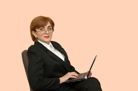 Businesswoman in the black business suit sitting on a chair working on the laptop photo
