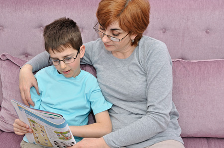 Woman helping young schoolboy to do his homework photo
