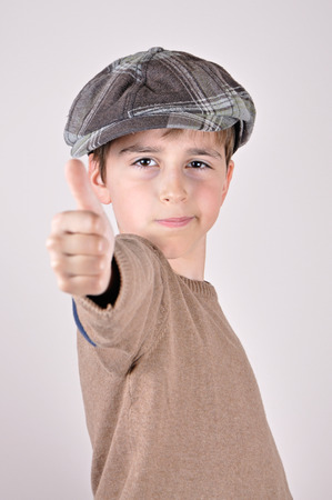 newsboy cap: Young boy with a newsboy cap showing thumbs up