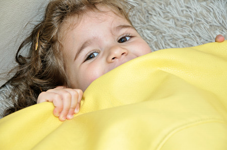 Sweet young girl playing with a flat yellow lazy bag photo