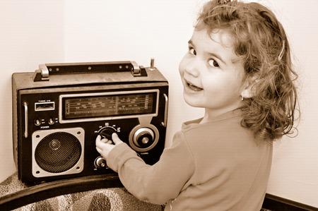 甘い若い女の子とレトロなほこりの多いラジオ